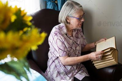 Senior woman reading book while sitting in nursing home