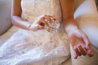 Midsection of bride spraying perfume on hand