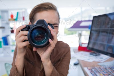 Female executive taking a photograph from digital camera