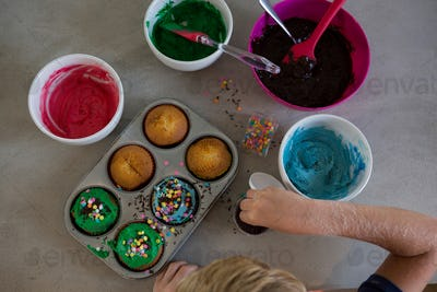 Cropped hand of boy decorating cupcakes with sprinklers