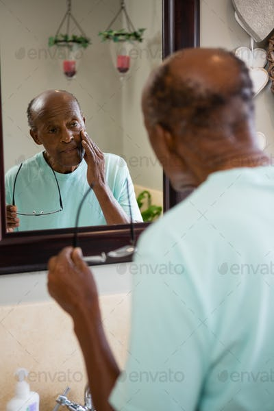 Concerned senior man touching cheek while looking into mirror