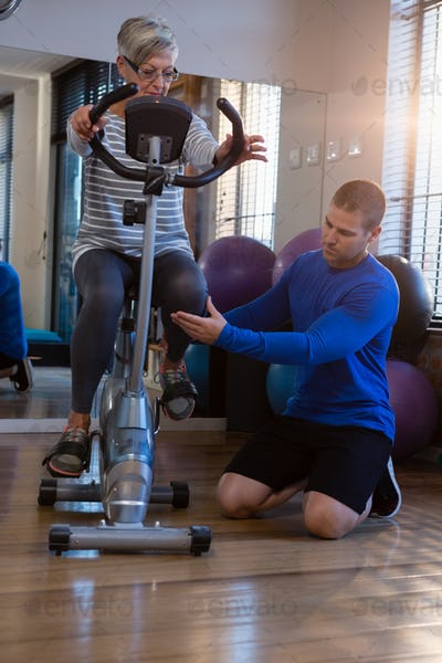 Physiotherapist assisting senior woman in performing exercise on exercise bike