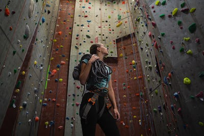 Female athlete carrying rope looking up while standing in gym
