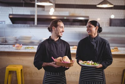 Smiling young wait staff looking at each other while holding fresh food in coffee shop