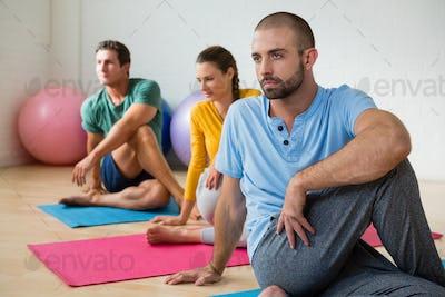 Yoga instructor guiding students in practicing Ardha Matsyendrasana