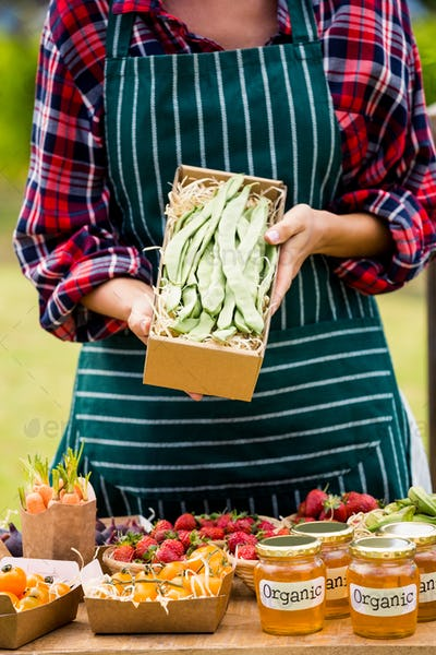 Midsection of woman holding box with vegetables