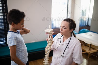 Boy looking at female therapist explaining with artificial spine
