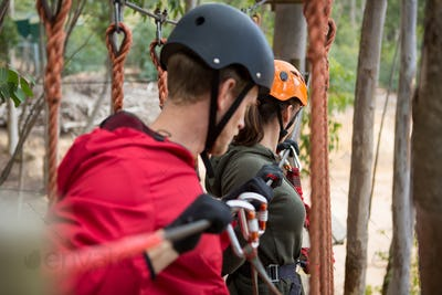 Young couple holding zip line cable while crossing obstacle in the forest