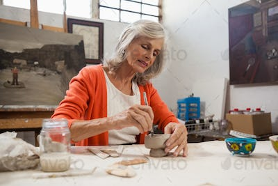 Attentive senior woman shaping a clay pot