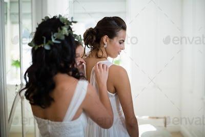 Bridesmaid assisting bride to dress