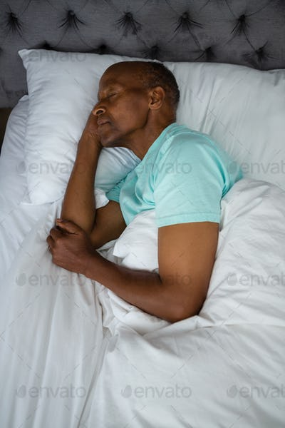 Overhead view of senior man sleeping on bed