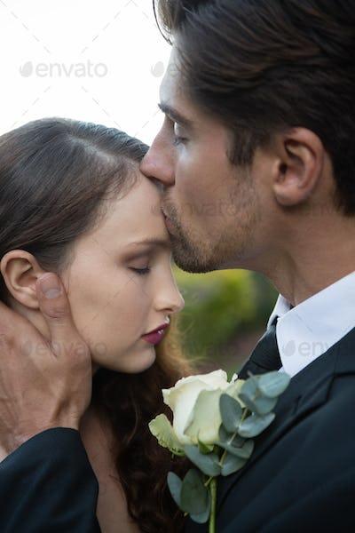 Groom kissing on bride forehead