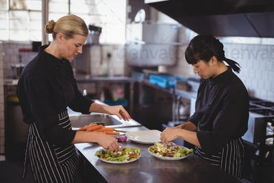 Confident young female chefs preparing Greek salad at kitchen counter