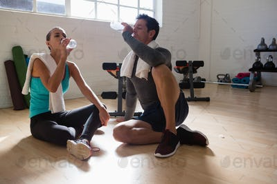 Tired athletes drinking water while sitting in gym