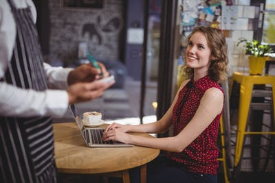 Midsection of waiter holding notepad while standing by smiling young female customer