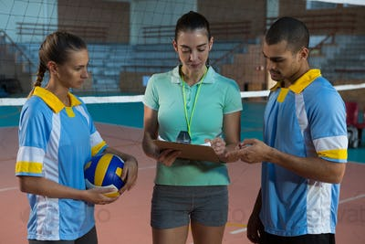 Coach discussing with volleyball players