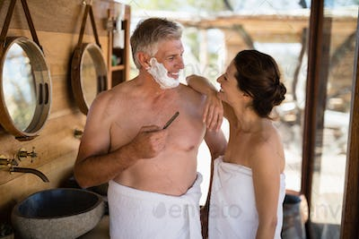 Smiling couple interacting while shaving in cottage