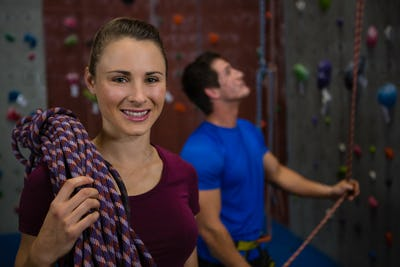 Athlete carrying rope while trainer climbing wall at gym