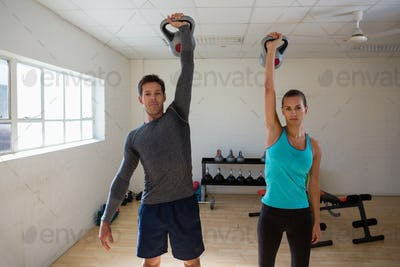 Portrait of athletes lifting kettlebells in gym