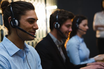 Business executives with headsets using computers at desk