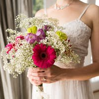 Midsection of smiling bride in wedding dress holding bouquet at home