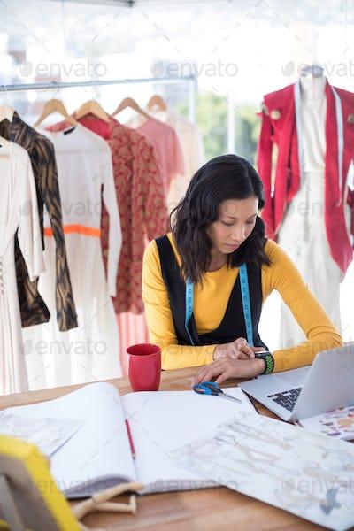 Female designer adjusting smart watch