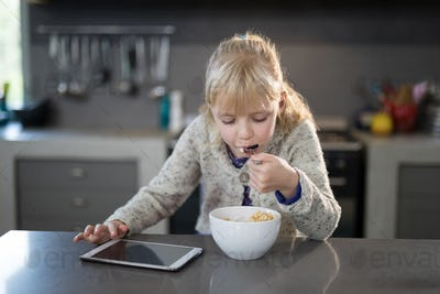 Little girl eating cereals rings with spoon from a bowl