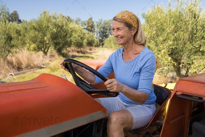Happy woman sitting in tractor