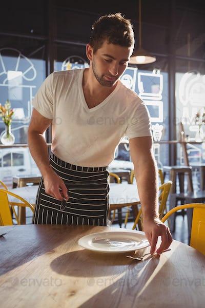 Waiter arranging utensils on table in cafe
