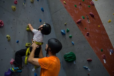 Trainer assisting boy in rock climbing