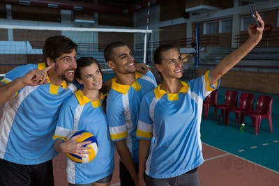 Female volleyball player with team taking selfie