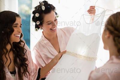 Smiling women looking at wedding dress