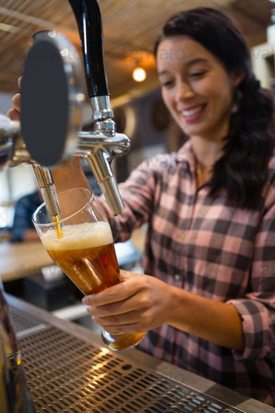 Pretty barmaid pouring beer from tap in glass