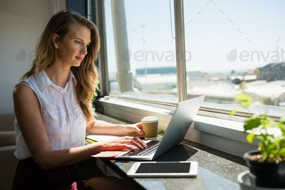 Young businesswoman working while using laptop