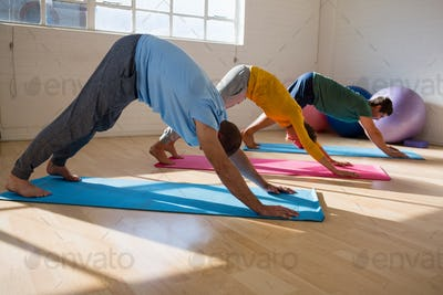 instructor with students practicing downward facing dog pose in yoga studio