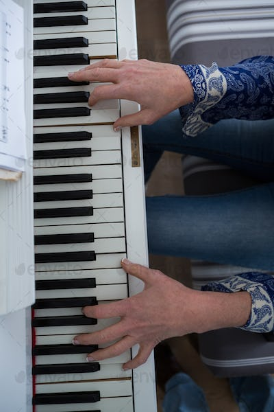 Mid section woman playing piano