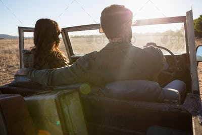 Rear view of couple in off road vehicle on sunny day