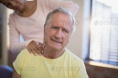 Senior male patient frowning while receiving neck massage from therapist