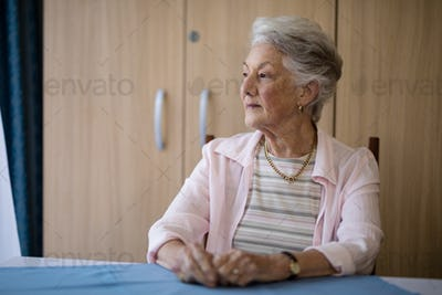 Thoughtful senior woman sitting at table