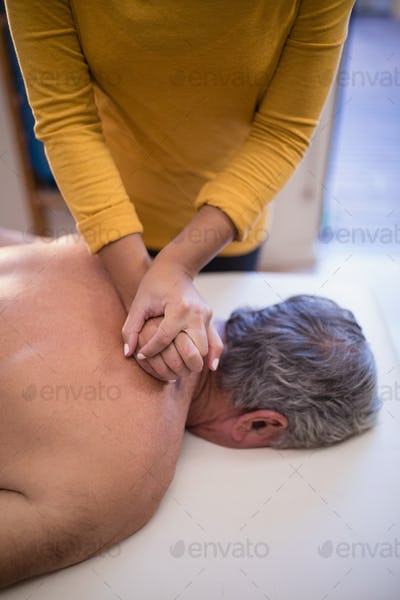 High angle view of female therapist giving neck massage to shirtless male patient