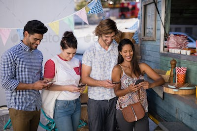 Friends using mobile phone at counter
