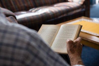 Hand of senior man reading book in nursing home
