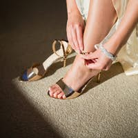 Low section of bride wearing golden sandals at home