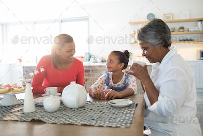 Happy multi-generation family having tea in dining table