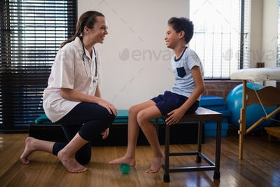 Smiling female therapist kneeling by boy stepping on stress ball