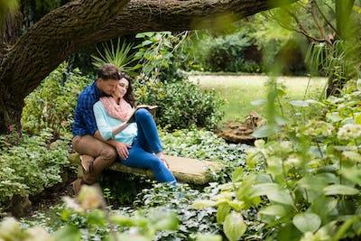Romantic couple reading book on bench in garden
