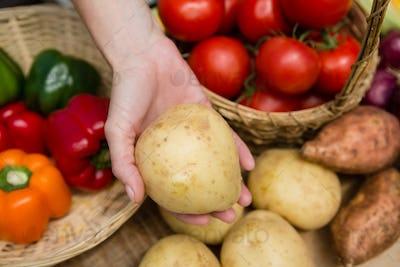 Woman holding fresh potato at vegetable stall