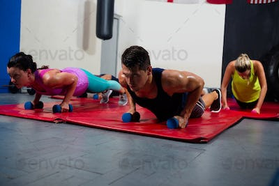 Young male and female athletes practicing push ups on dumbbells