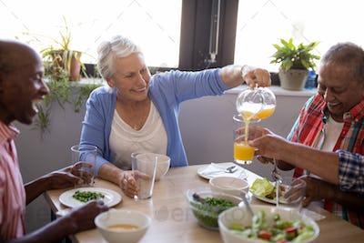 Smiling senior woman serving juice to friends