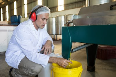 Technician examining olive oil produced from machine